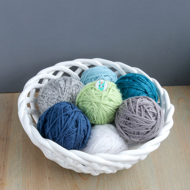 Several balls of yarn displayed in a ceramic bowl