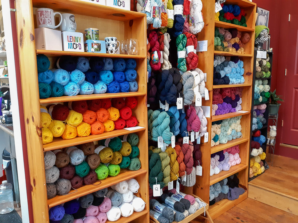 Image of yarn displayed on shelves and hanging on the wall