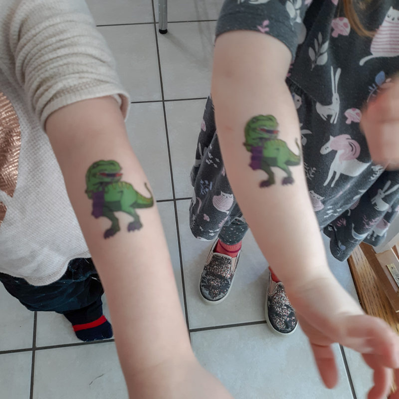 Picture of kids' arms with a temporary tattoo of a t-rex knitting