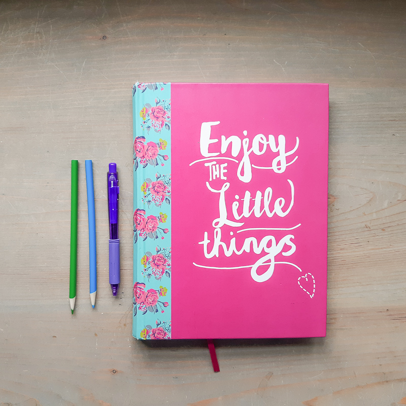 "on a wood neutral table, a notebook that says ""Enjoy the little things"" with a gel pen and 2 color pencils"