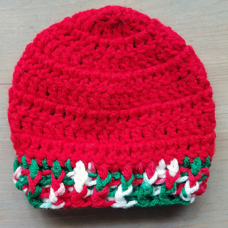 Example of the perfect newborn crochet hat in red, green, white on flat lay.